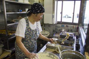 入口横にある天ぷらブースで、天ぷらを揚げ続ける女将さん。