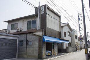 仏生山のお成り街道沿いにある店舗跡。壁の上部に残る看板と、青いテントが営業当時の名残です。
